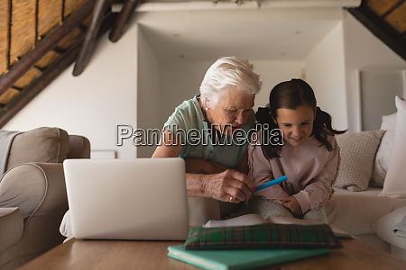 grandmother helping her granddaughter with homework