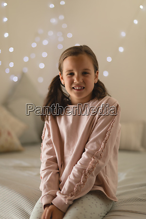 innocent girl sitting in bedroom at