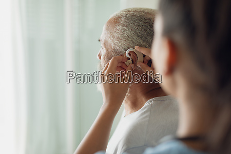 healthcare worker putting hearing aid