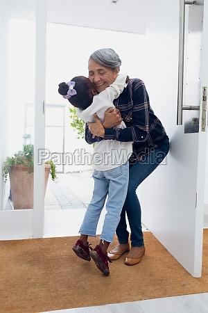 girl hugging grandmother by the door