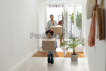 family with cardboard boxes entering their