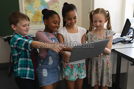 group of happy schoolkids studying on