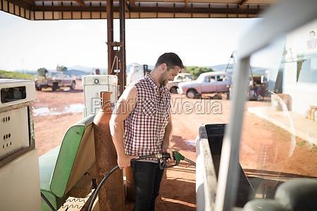 man filling petrol in car at
