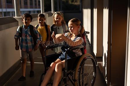 disable schoolgirl using smartphone in hallway