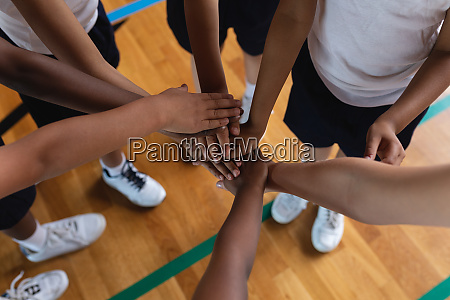 schoolkids forming hand stack at basketball