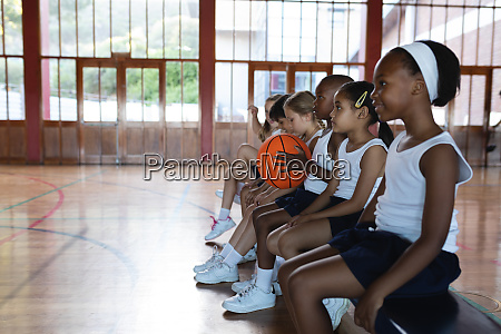schoolkids sitting on bench at basketball