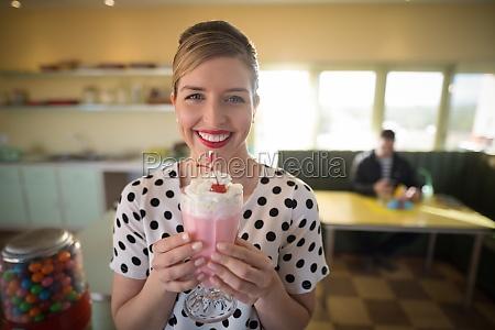woman having milkshake in restaurant