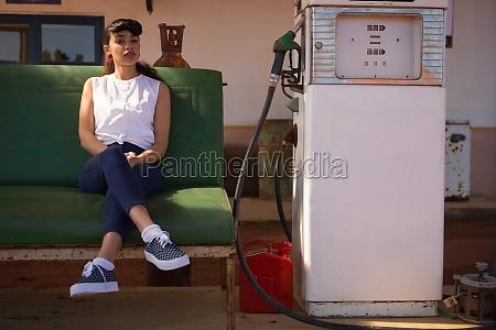 woman relaxing at petrol pump station