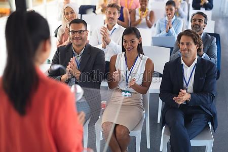 business people applauding female speaker in