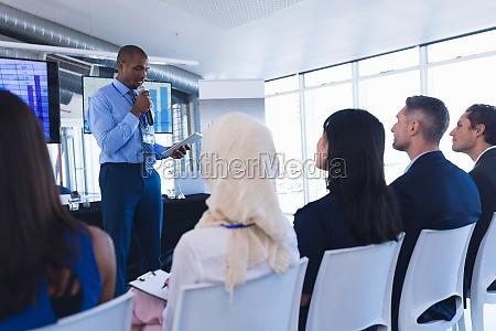 male speaker with digital tablet speaks