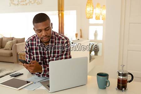 man using mobile phone and laptop