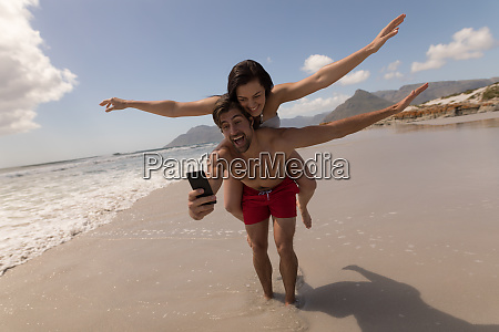 young couple piggyback with arms outstretched