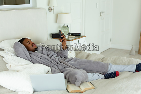 man using mobile phone while relaxing