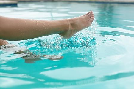 woman splashing water in swimming pool
