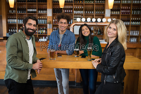 smiling friends having glass of beer