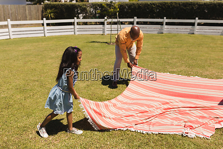 grandfather and granddaughter placing picnic blanket