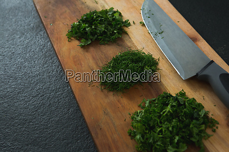 chopped herbs with knife on chopping