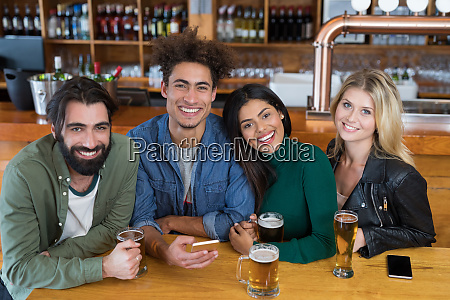 happy friends using mobile phone while
