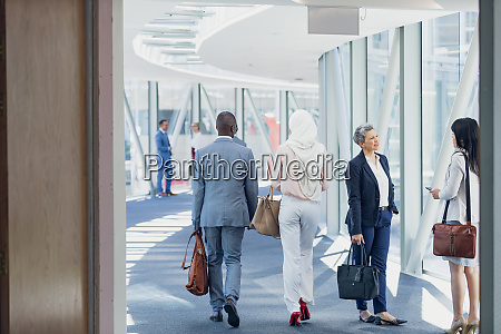 business people walking in corridor in