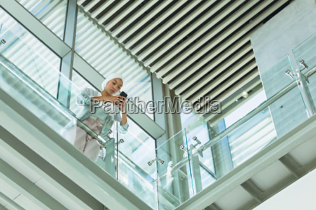 businesswoman in hijab leaning on railing