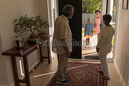 grandparents standing near door and inviting