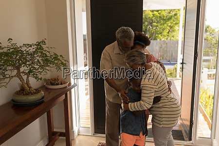 grandparents embracing their grandchildren at home