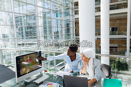 females executives discussing over computer at