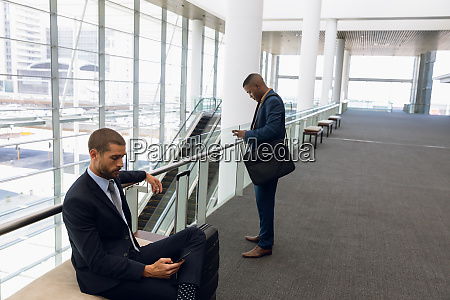 travelling businessmen using smartphones in a