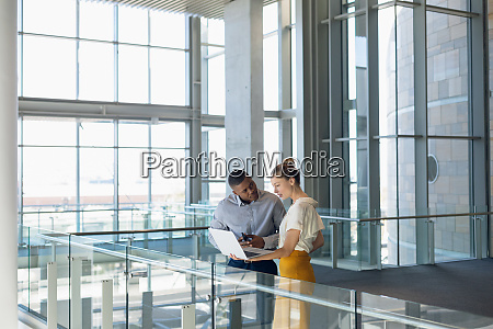 two young business people stand working