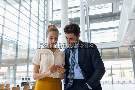 two business people looking at phone