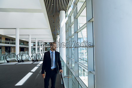 businessman looking out of window in