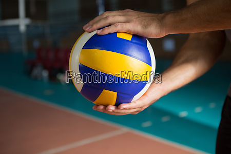 cropped hands of player holding volleyball