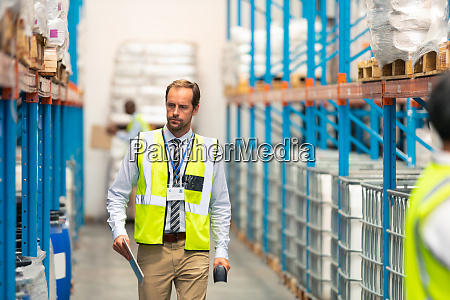male supervisor walking in warehouse