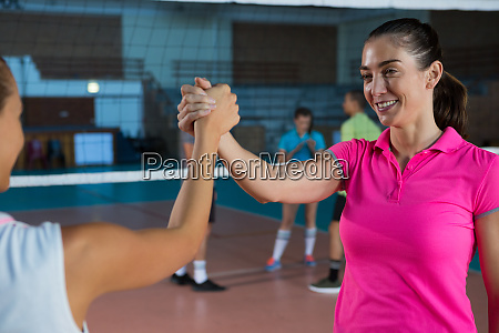 determined volleyball players holding hands