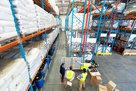 warehouse staff discussing over whiteboard in