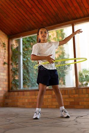 schoolgirl spinning a hula hoop around