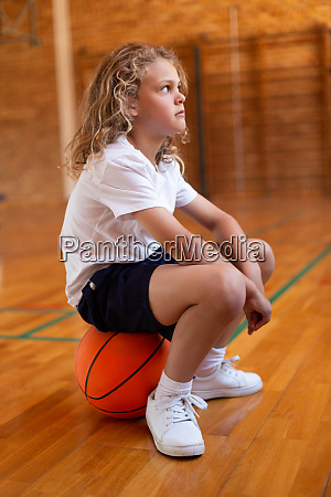 schoolgirl sitting on a basketball in