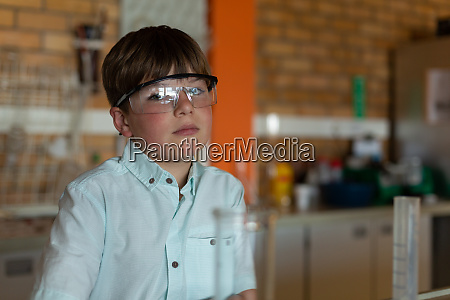 schoolboy with protective eyewear looking at