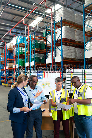 staffs discussing over document in warehouse