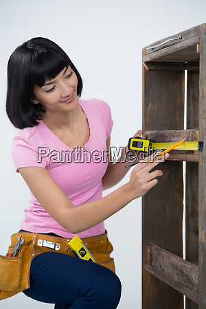 woman measuring furniture with tape measure