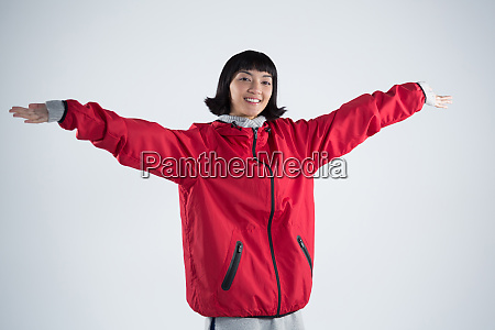 smiling woman standing with arms outstretched