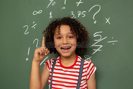 schoolgirl standing against green board in