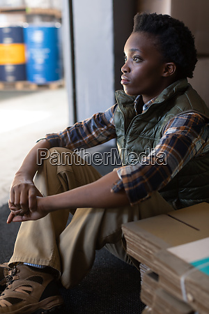 thoughtful female worker sitting in warehouse