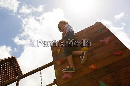 schoolgirl climbing a wall in the