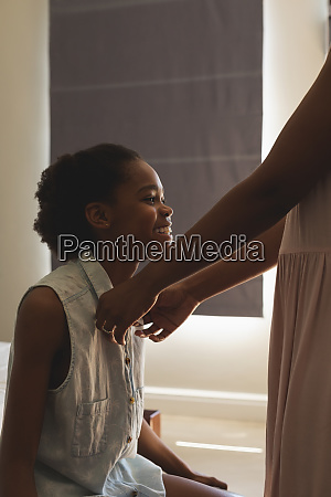 african american mother helping her daughter