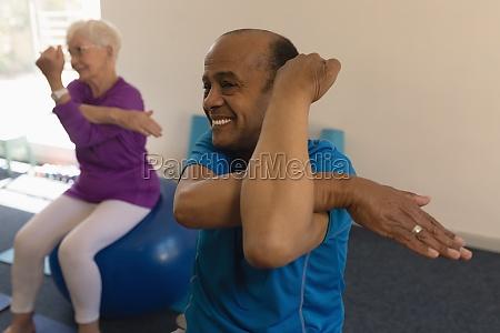 senior man exercising in fitness studio