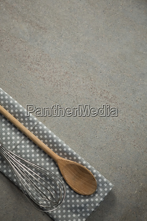 wooden spoon with wire whisk on