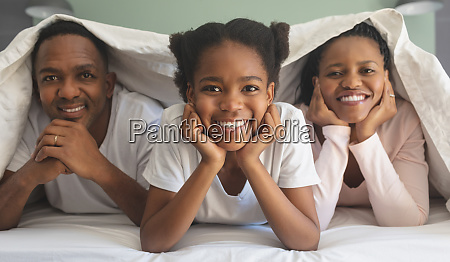 happy african american family under blanket