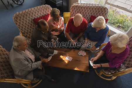group of senior friends playing cards