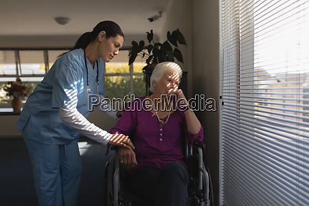 female doctor consoling sad disable senior